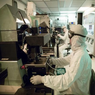 Researchers in white protective gear working in a clean room