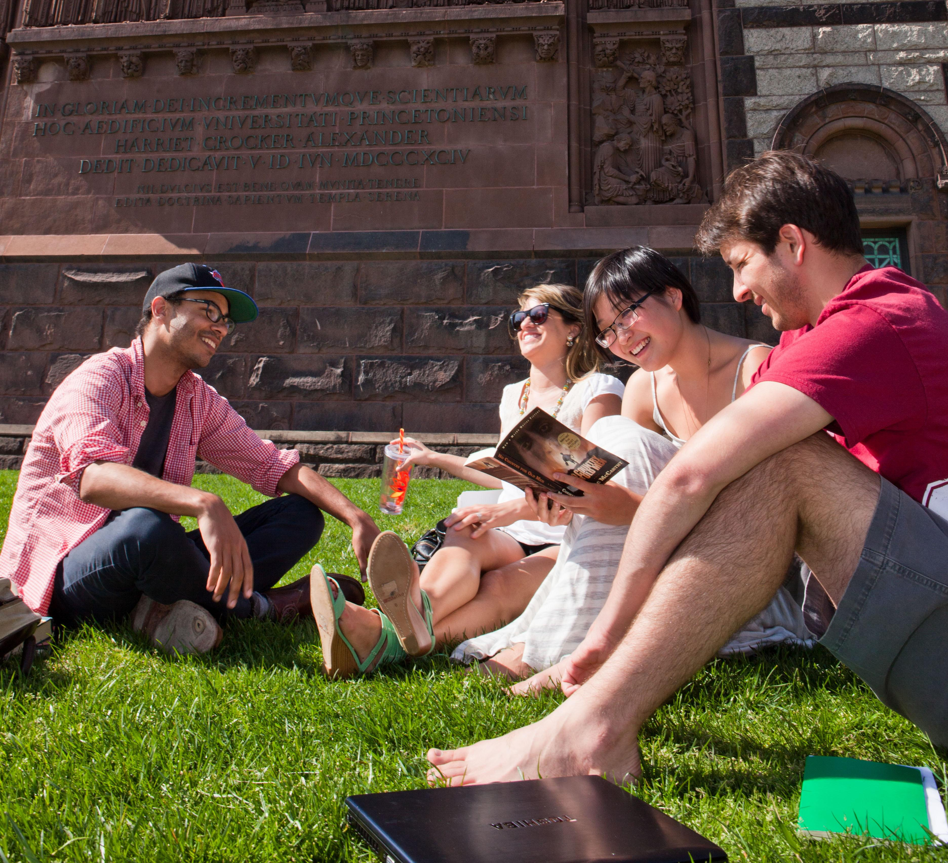 Group of 4 students sitting outside near Alexander Hall on a spring day