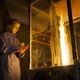 Mechanical and Aerospace Engineering researcher at Princeton University wearing safety goggles observing a large flame in a glass case.